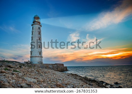 Lighthouse searchlight beam through sea air at night. Seascape at sunset - stock photo