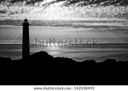 lighthouse silhouette in black and white - stock photo