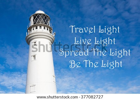 Lighthouse with a Inspirational motivational quote.of Travel Light, Live Light, Spread The Light and Be The Light against a partly cloudy sky background - stock photo
