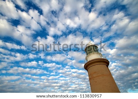 Lighthouse with blue sky and white cloud background - stock photo