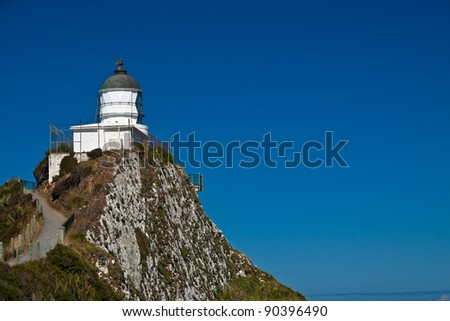 Lighthouse with bright blue sky. Nugget Point Lighthouse, New Zealand. - stock photo