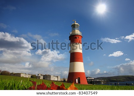 Lighthouse with red autumn leaves, Plymouth, UK - stock photo