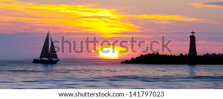 Lighthouse with searchlight beam - stock photo