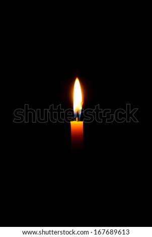 Lighting candles on a black background. - stock photo