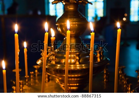 lighting fire candles in russian orthodox church - stock photo