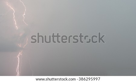 Lighting on a grey stormy sky. Ideal as a background with plenty of copy space. - stock photo