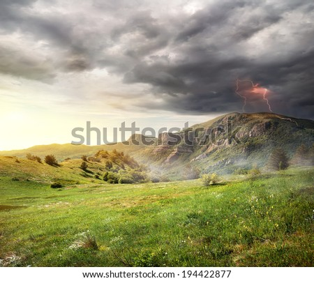 Lightning and storm clouds over the mountains - stock photo