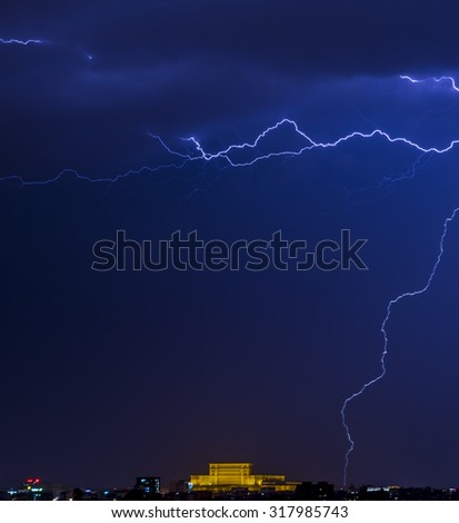 Lightning and thunderstorm above night city with the Palace of the Parliament in center, Bucharest, Romania - stock photo