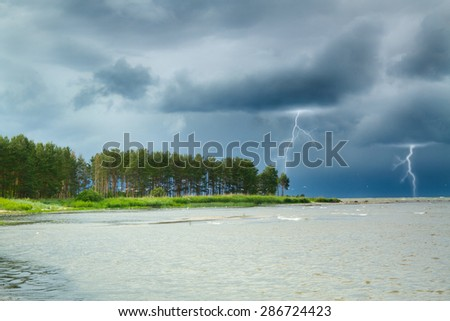 Lightning at sea. summer storm coming ashore. the waves beating against the rocks - stock photo