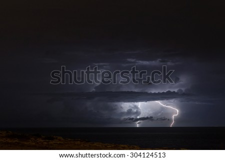 Lightning bolt and storm clouds during a thunderstorm in Malta - stock photo
