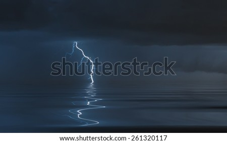 lightning bolts reflection over the ocean - stock photo