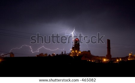 Lightning display over an industrial plant - stock photo