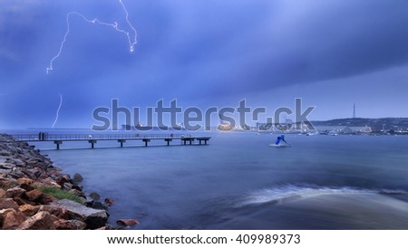 Lightning, storm and rain over Esperance sea bay and coast with cargo port terminals, cranes and ships behind town bay waters. - stock photo