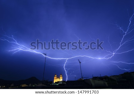 Lightning Storm at Velez-Rubio village, Spain, dark blue sky with bright electrical flash, thunder and thunderbolt, bad weather concept - stock photo