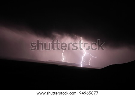 Lightning strike in the darkness over mountains - stock photo