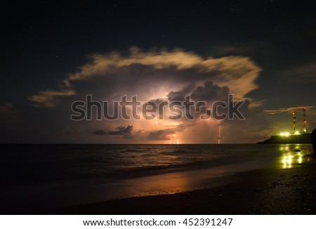 lightning strike in the darkness, storm on the sea - stock photo