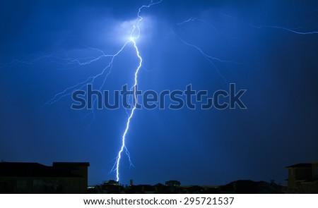 Lightning Strike on a Dark Blue Sky Hitting Building in Distance - stock photo
