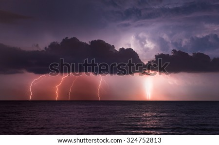 lightnings in dark sky, stormy sea  - stock photo