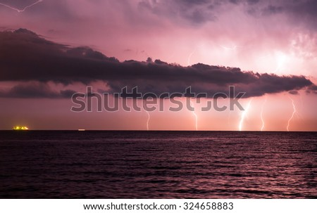 lightnings in dark sky, stormy sea against cargo Ships - stock photo