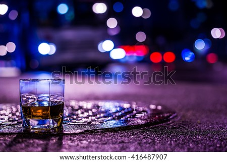 Lights of the city at night through the glass of alcohol, the night avenue with driving bus. View from the glass level with brandy standing on the wet manhole, in blue tones - stock photo