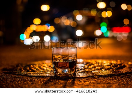 Lights of the city at night through the glass of alcohol, the night avenue with driving buses. View from the glass level with brandy standing on the wet manhole - stock photo