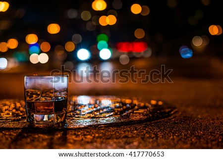 Lights of the city at night through the glass of alcohol, the night avenue with driving car. View from the glass level with brandy standing on the wet manhole - stock photo