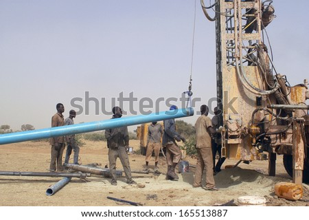 LIGUIDIMALGEM,  BURKINA FASO - FEBRUARY 24: In Africa the water is underground, workers bring another tube to add in drilling, February 24, 2007 - stock photo