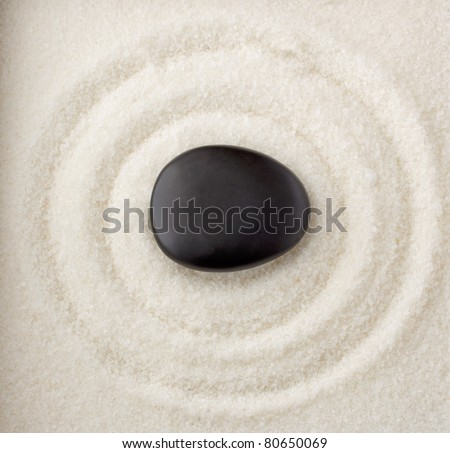 Liittle black stone at center of circles of white sand - stock photo