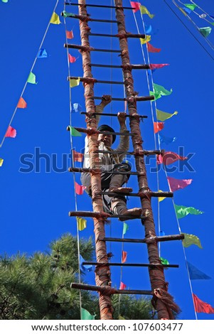 LIJIANG, CHINA - DECEMBER 8, 2010: A barefooted Naxi ethnic man climbs up a ladder made of sharp knives at the Dongba Valley Cultural Village on December 8, 2010 in Lijiang, Yunnan Province of China. - stock photo