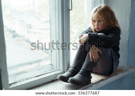 Like a shag on a rock. Poor depressed hopeless girl folding her legs and sitting on the window sill while feeling unhappy - stock photo