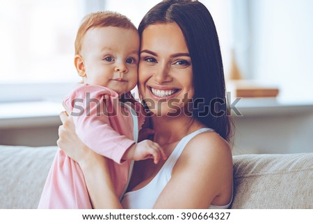 Like mother like daughter. Cheerful beautiful young woman holding baby girl in her hands and looking at camera with smile while sitting on the couch at home - stock photo