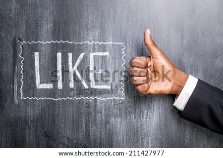 Like this! Close-up of human hand with thumb up in front of the blackboard with inscription Like  - stock photo
