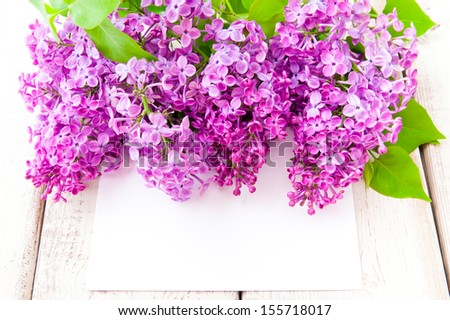 Lilac blossoms with card  on wooden table - stock photo