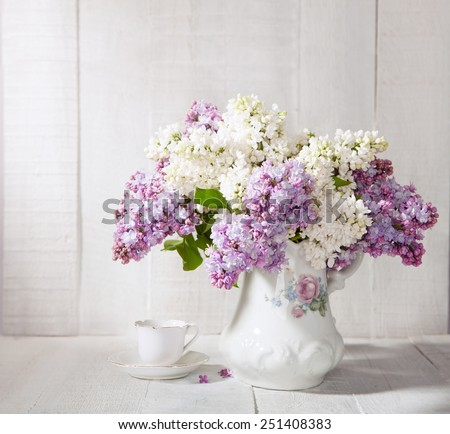 Lilac Bouquet  in old ceramic jug  and cup of coffee   against a white wooden table.  - stock photo