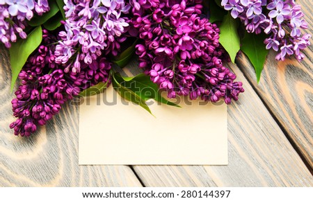 Lilac flowers with empty tag on a old wooden background - stock photo