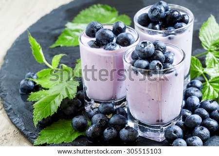 Lilac homemade yogurt with blueberries on a dark background, selective focus - stock photo