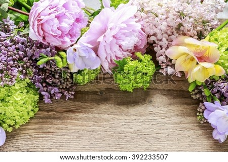 Lilacs, peonies and green guelder rose (viburnum opulus) on wooden background, copy space - stock photo