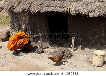 LILIIR, SOUTH SUDAN-DECEMBER 4 2010: Unidentified woman in the village of Liliir, South Sudan puts new mud on her home. - stock photo