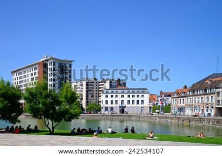LILLE, FRANCE - JULY 17, 2014: The Quai du Walt, on the River Deule, in Lille, France. Formerly an inland port, it is now an open-air, waterside leisure and recreation green space, with cafes, etc. - stock photo