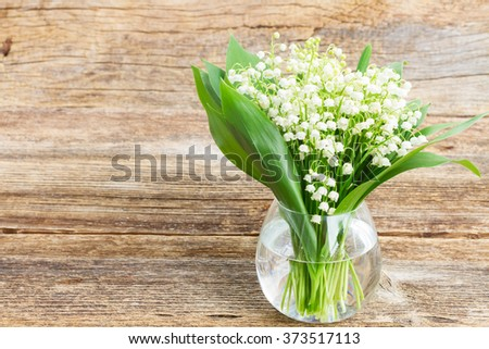 Lilly of valley in glass vase on wooden table  - stock photo