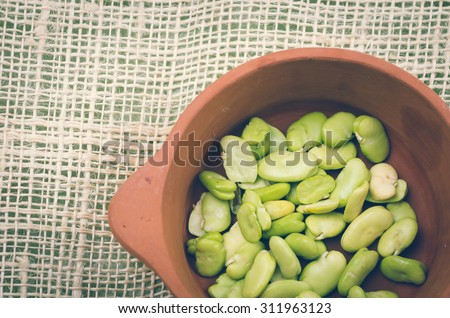lima beans inside ceramic terracota bowl and rustic background. - stock photo