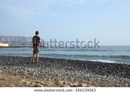 LIMA, PERU - APRIL 2, 2012: Unidentified young man standing on the rocky Pacific coast of Miraflores watching in the direction of the district of Chorrillos on April 2, 2012 in Lima, Peru.  - stock photo