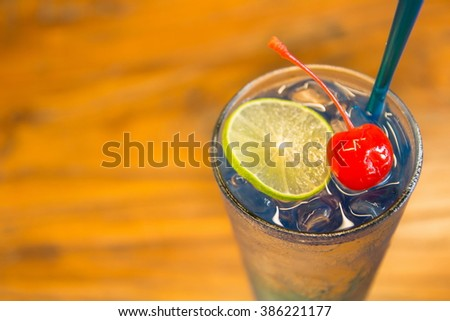 Lime and cherry on Blue Curacao cocktail - stock photo