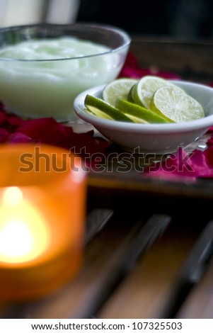 Lime and massaging oil, most important ingredient used in spa treatment (shallow depth of field) - stock photo