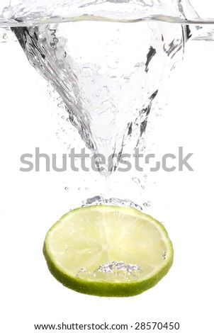 Lime dropping into water with a splash - stock photo