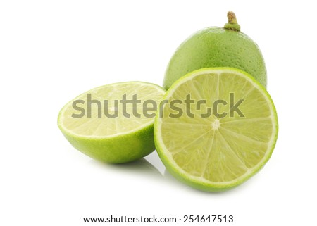 lime fruit and a cut one on a white background - stock photo