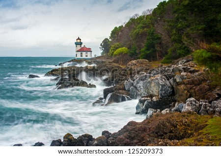 """Lime Kiln Lighthouse. A stormy day on San Juan Island, Washington. Waves crash against the rocky coastline.The long exposure makes the water look """"silky"""". - stock photo"""
