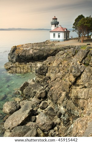 Lime Kiln Lighthouse on San Juan Island with rocks in foreground - stock photo