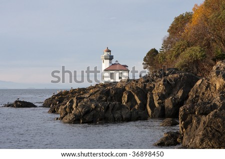 Lime Kiln lighthouse, surrounded by the rocky coastline, is illuminated by the warm light of a late autumn sunset. - stock photo