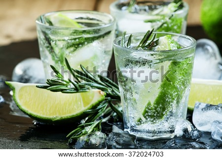 Lime Lemonade with rosemary and ice, dark toned image, selective focus - stock photo